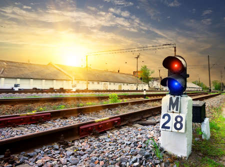 railway transportation: Railway semaphore near industrial station at sunset Stock Photo