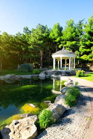 city park pavilion: White arbour near beautiful lake in park Stock Photo