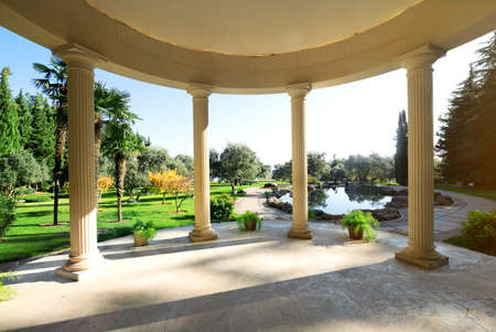 arbour: Arbour with columns near lake in the park Stock Photo