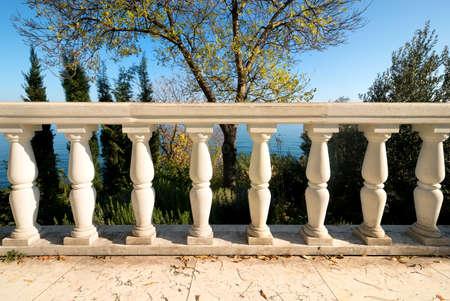 city park pavilion: Decorative columns on a viewpoint deck near sea
