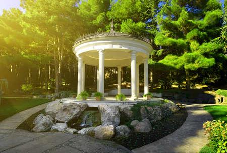 city park pavilion: White bower among the coniferous trees in park