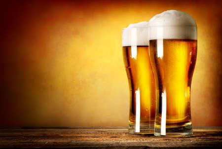 tomando alcohol: Dos vasos de cerveza en una mesa de madera