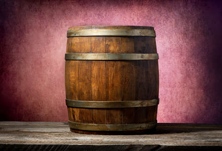 distillery: Wooden barrel on a table and pink background