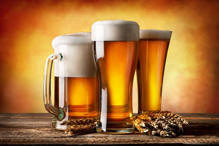 Three beers and wheat on a yellow background Stockfoto