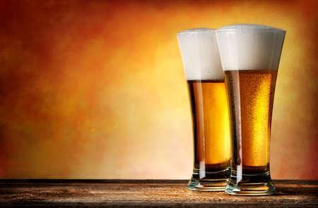 黄色の背景にビールを二杯 写真素材