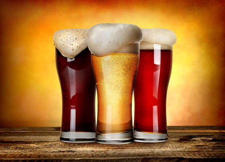 Three sorts of beer on a wooden table Banco de Imagens