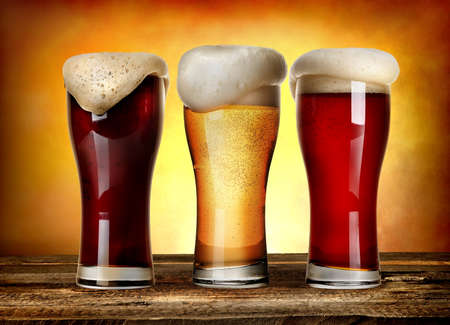 vasos de cerveza: Tres vasos de cerveza en una mesa de madera
