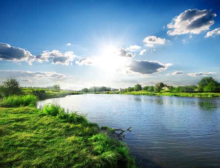春の朝の穏やかな川に架かる太陽 写真素材