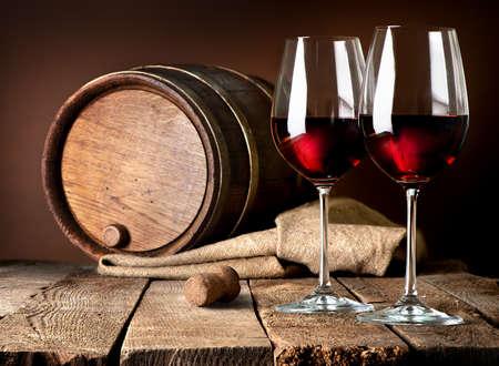 barra de bar: Barril y copas de vino tinto sobre una mesa de madera