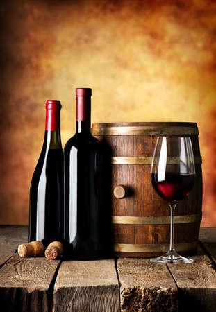 copa de vino: Las botellas y barricas de vino en una mesa de madera