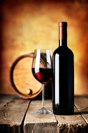 Red wine in bottle and cask on a wooden table Stock Photo