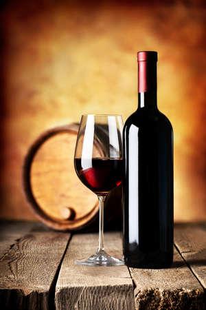 botella de licor: Vino en botella y barril en una mesa de madera Foto de archivo