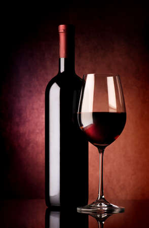 Wine in wineglass and bottle on vinous background Banco de Imagens
