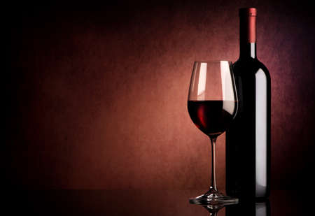 Red wine in bottle and wineglass on vinous background