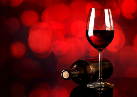Red wine in wineglass and bottle on red background Standard-Bild