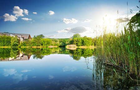bilding: Village by the calm river in spring