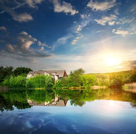 bilding: Sunset over village near the calm river