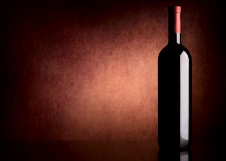 Bottle with wine on a vinous background