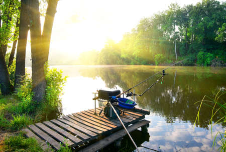 fishing pier: Fishing on a calm river in the morning