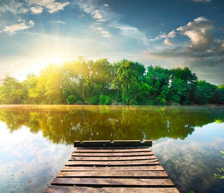 reflexion: Muelle de pesca en un río en la salida del sol Foto de archivo