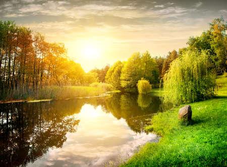 táj: Naplemente nyugodt folyón a parkban