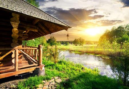cabaña: Casa de baños de madera cerca de lago en la puesta del sol