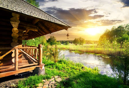 Wooden bathhouse near lake at the sunset