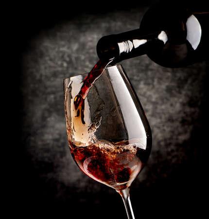 vino: Vino que vierte en la copa de vino sobre un fondo negro Foto de archivo
