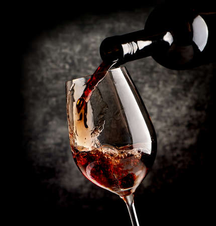 pouring wine: Wine pouring in wineglass on a black background