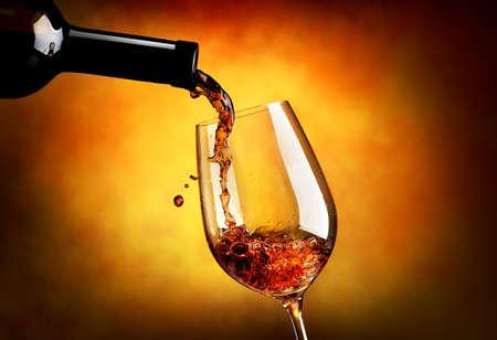 오렌지 배경에 와인 잔에 붓는 와인