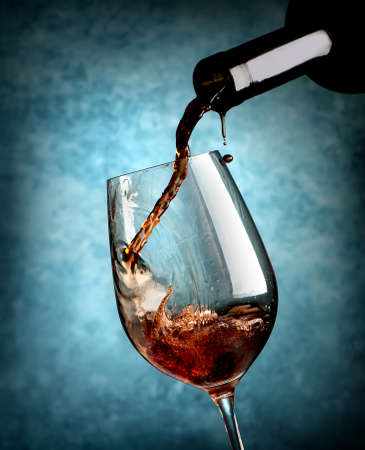 Wine pouring in wineglass on a blue background