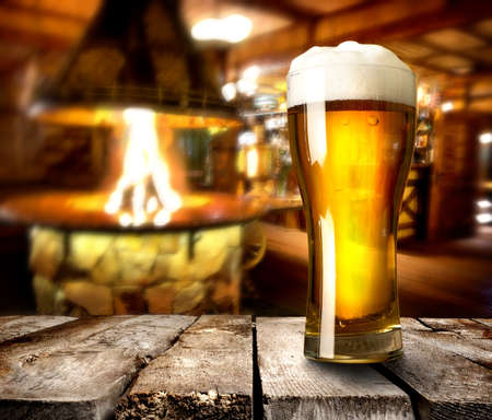 cosiness: Beer on wooden table in bar with furnace