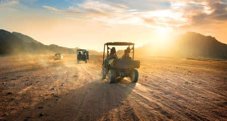 desert sun: Buggies in sand desert at the sunset Stock Photo