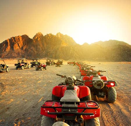 일몰 사막에서 쿼드 자전거