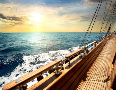 deportes nauticos: Barco de vela en el mar rojo en la puesta de sol