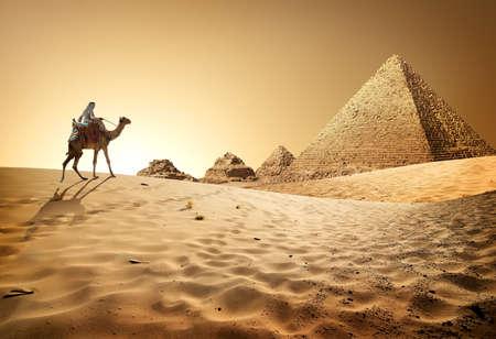 Bedouin op kameel in de buurt van piramides in woestijn Stockfoto