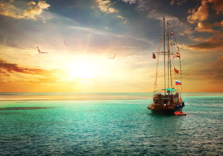 Hermosa puesta de sol sobre yate en el mar Foto de archivo