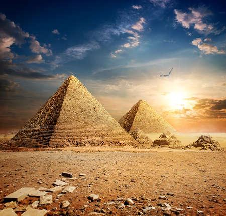 tumbas: Gran pájaro sobre pirámides de la puesta de sol Foto de archivo