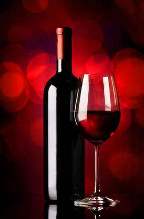 sektglas: Bottle and glass with red wine on red background