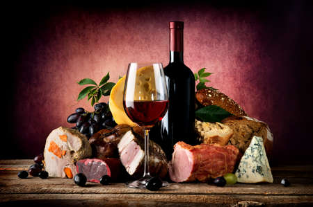 Red wine and different food on a wooden table Foto de archivo