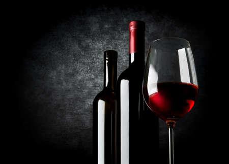 Due bottiglie di vino e bicchiere di vino su sfondo nero Archivio Fotografico - 44833939