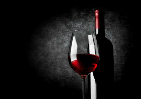 pouring wine: Wineglass of red wine on a black background Stock Photo