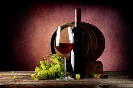 Delicious red wine with grape on wooden table