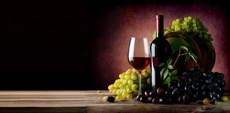 green bottle: Vine of grape with wine on wooden table Stock Photo