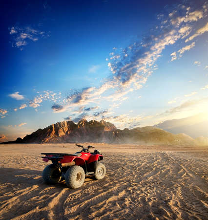 Quad bike in sand desert near mountain