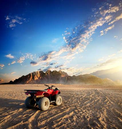 vacation destination: Quad bike in sand desert near mountain