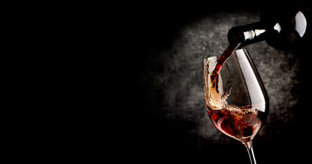 Wine pouring in wineglass on the black background 스톡 콘텐츠