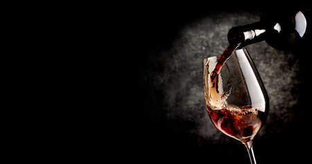 Vino che versa nel bicchiere di vino su sfondo nero Archivio Fotografico - 47037149