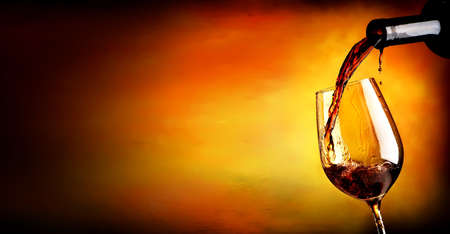 Wine pouring in wineglass  on an orange background Banque d'images
