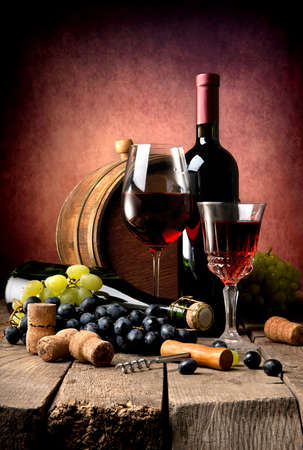 Red wine with grape and wooden cask on a wooden table